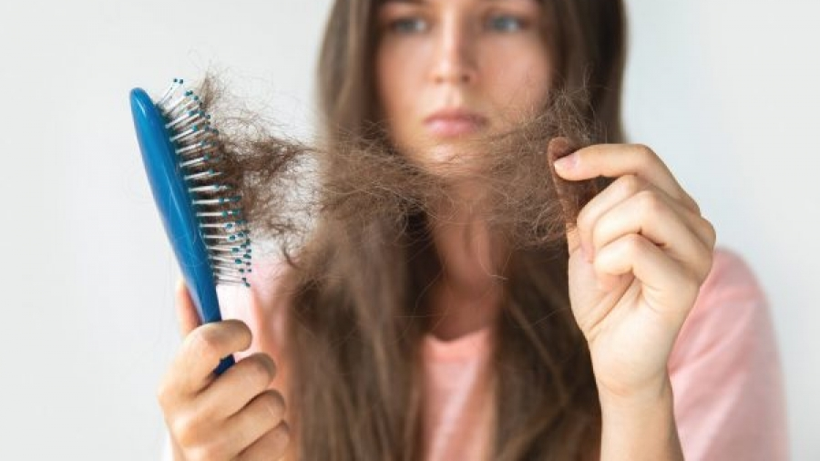 Young woman is upset because of hair loss